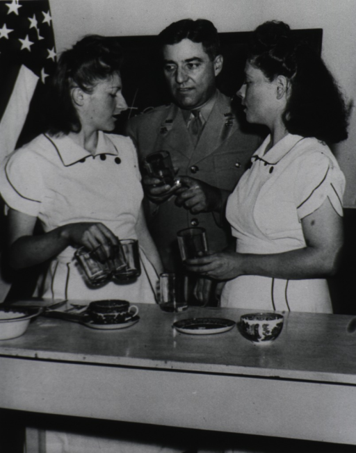 <p>Two waitresses observe as a man in uniform demonstrates the sanitary way to carry drinking glasses, he holds a glass by the bottom; as is the waitress on the right, the other waitress holds three glasses from the top with her fingers in the glasses.</p>