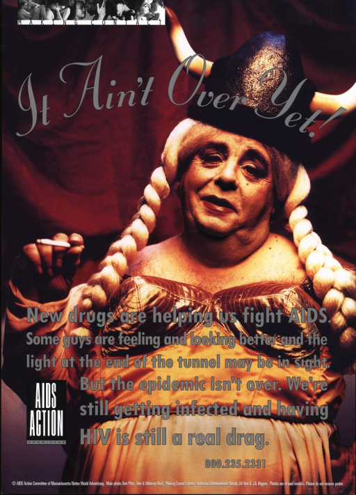 <p>An overweight, middle-aged man, made up and dressed as valkyrie Brunnhilde, complete with a blond wig and a viking hat, is holding a lit cigarette in his right hand. His message is that even though there are new drugs that are helping fight AIDS, the epidemic is not over. On the top of the poster are five small black and white photos of homosexual and heterosexual couples making love. The caption below these photos is: &quot;Making contact&quot;.</p>
