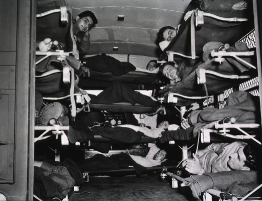 <p>A U-shaped formation of litters stacked four high is shown from the rear opened door of the ambulance.  Servicemen occupy each of the litters.  All are on their backs, some rest, while some smile for the camera.</p>