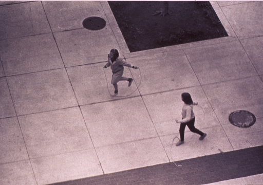 <p>Two girls jumping rope in the common area of a housing project.</p>