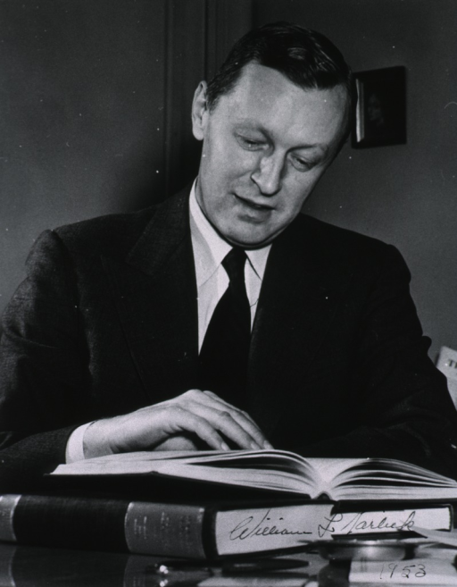 <p>Head and shoulders, full face; seated at desk; reading; right hand resting on open book.</p>
