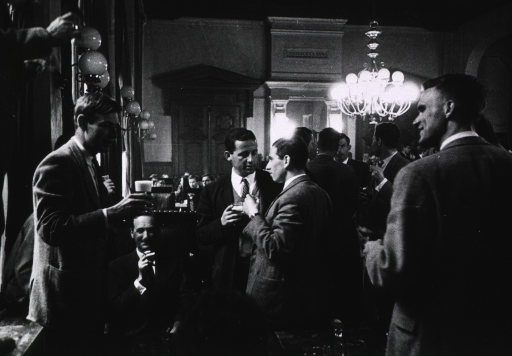 <p>Interior view: a large room (at a private club?) with a group of young men in suits drinking and socializing.</p>