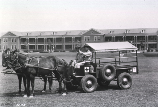 <p>A horse-drawn ambulance is shown on the lawn that spreads before a long three-storied building.  Two servicemen sit on the front seat, one of them holding the reins.  U.S. Army logos appear on the side of the ambulance.</p>