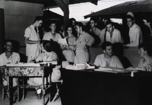 <p>A group of servicemen gathers around the desks of female Red Cross employees.</p>