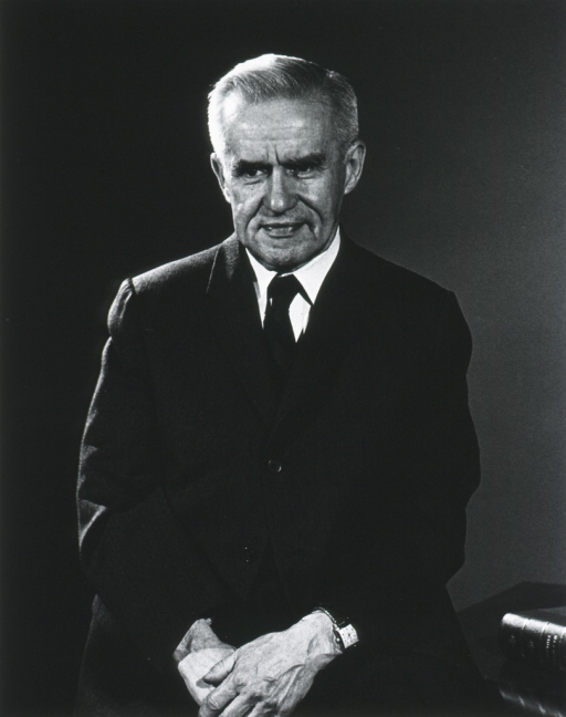 <p>Half-length, full face, leaning against a table with hands clasped in front of him, wearing dark suit and tie.</p>