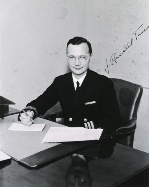 <p>Seated, full face, pencil in hand, uniform, commander.</p>