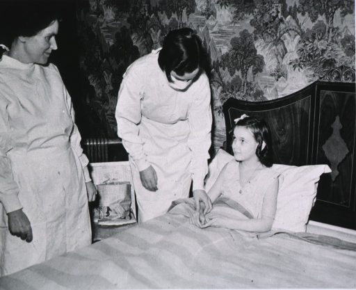 <p>Showing a young girl in bed having her pulse taken by a nurse.</p>