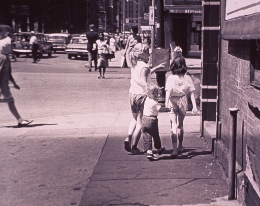<p>Three little girls are walking down a city sidewalk.</p>