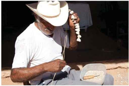 "Chalo, a Mayo indian craftsman shakes and inspects a string of Rothschildia cocoons for just the right sound, effectively ""tuning"" the rattles."