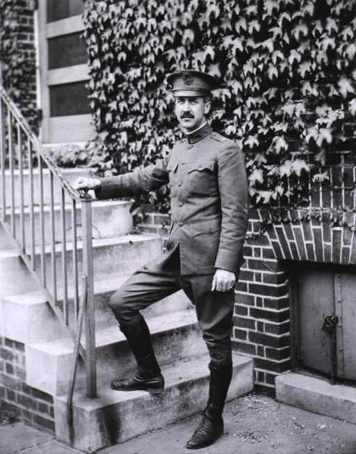 <p>Full length, standing at base of stairway, right foot on first step, right hand on iron railing.  Wearing Army uniform and cap.</p>