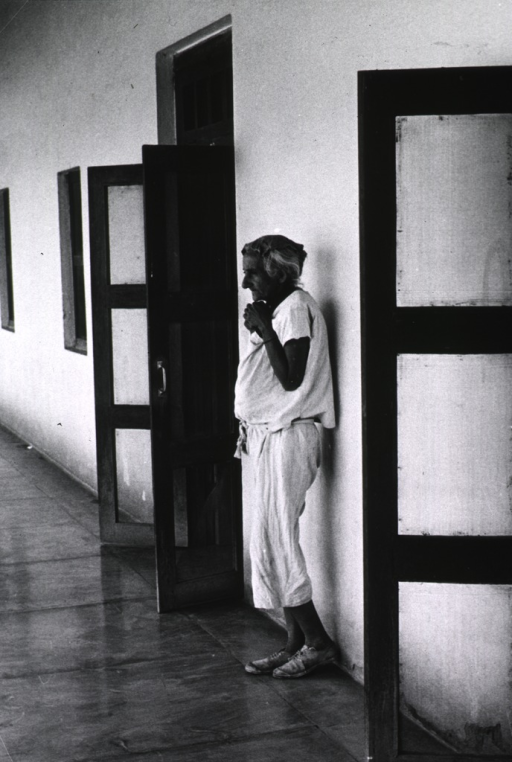 <p>An old woman is standing against a wall; she is holding her arms close to her chest.</p>