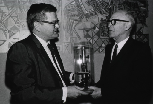<p>Showing the presentation by Dr. Robert W. Coon, of the microscope used by Dr. James Ewing while conducting cancer research, to Senator Lister Hill.</p>
