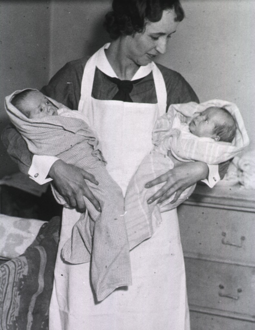 <p>View of a nurse holding two infants.</p>