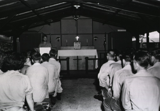 <p>Men and women in uniform sit on benches and listen as the chaplain speaks from a podium.</p>