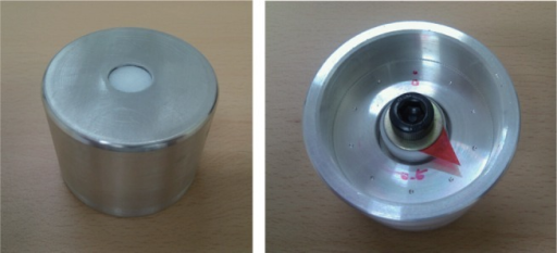 Photograph of the custom-made aluminum mold with a movable Teflon plate attached to a bolt.