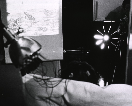 <p>Interior view: electrodes are attached to a patient's head to record the physiological response to various stimuli. The patient is only barely visible (seen from behind), but appears to be facing a movie camera that is recording the physical response.</p>