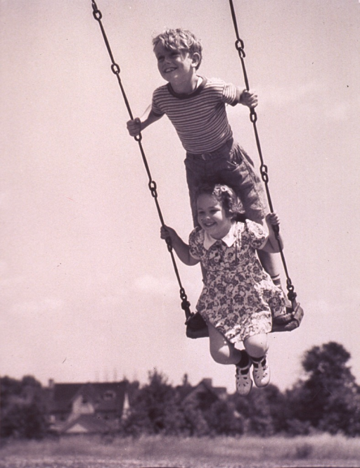 <p>A boy and a girl are on a swing.</p>