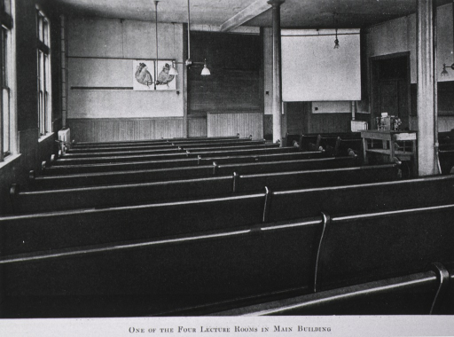 <p>Interior view: rear view of room with wainscoting; pews facing a black board and a movie screen.</p>