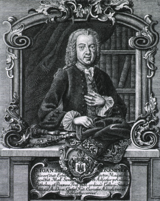 <p>Half-length, standing, right pose, full face, wearing velvet coat and lace; bookshelves in background; coat-of-arms.</p>
