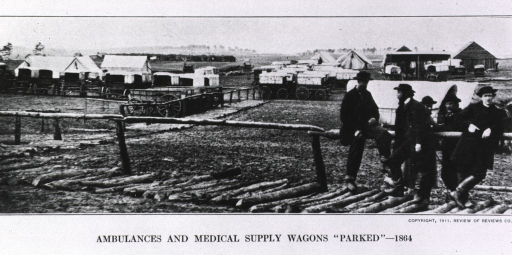 <p>Panoramic view showing a small group of men leaning on a rail fence, behind them are many wagons parked near some buildings and tents.</p>