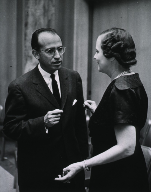<p>Dr. Jonas Salk, standing and talking with Mrs. Mary Lasker.</p>