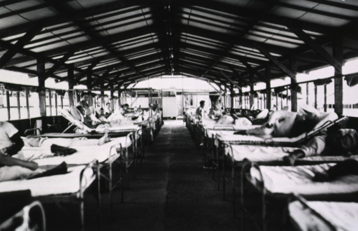 <p>Wounded servicemen recline in beds that line either side of a long open-air ward.  Several female nurses can be seen administering to the patients.</p>