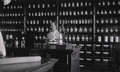 <p>An interior view of the dispensary at the Naval Hospital.  A staff person stands behind the counter.</p>