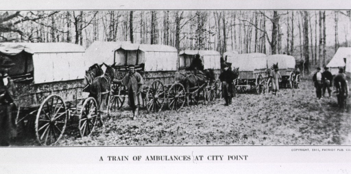 <p>Several horse-drawn ambulances, ready for action, are parked in a line in a wooded area; several men are moving about.</p>