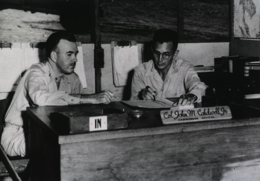 <p>The two servicemen sit at a desk and confer over notes.</p>
