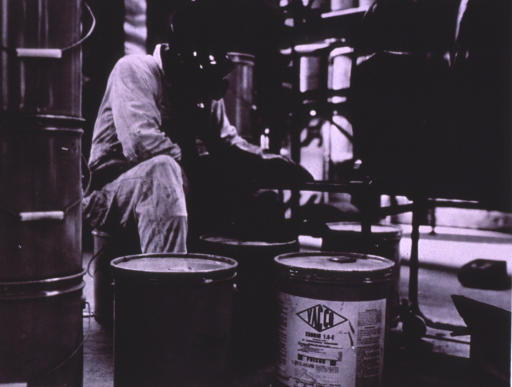 <p>A worker wearing coveralls, mask, and goggles sits among large cans of pesticides.</p>