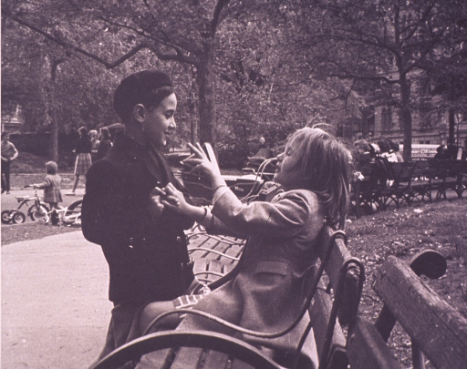 <p>A boy is taunting a girl sitting on a park bench.</p>