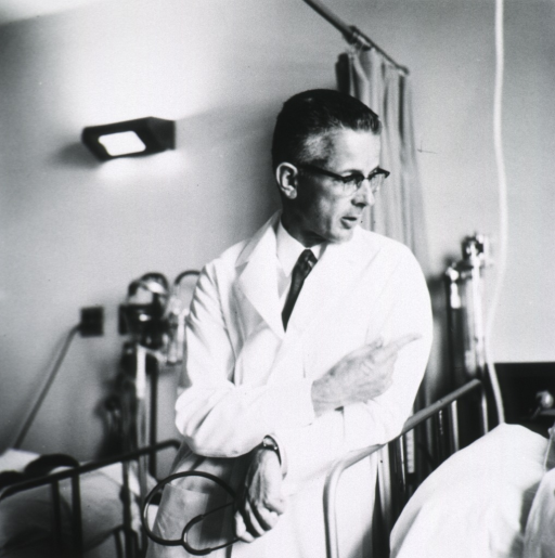 <p>Half-length, front pose, head turned to the right, standing at end of patient's bed; wearing glasses and white lab coat; holding stethoscope.</p>