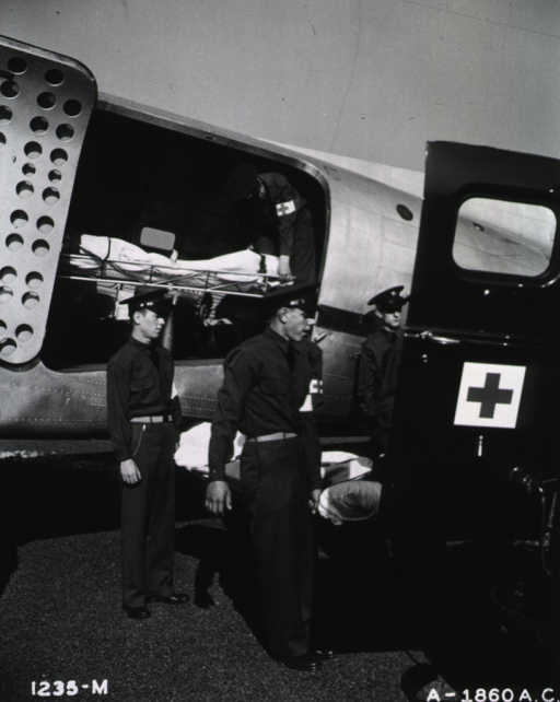 <p>Servicemen remove wounded servicemen on stretchers from an airplane and place them into an adjacent ambulance at an unspecified location.</p>