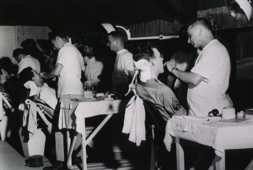 <p>Servicemen in uniform sit in chairs while they receive dental treatment from dentists and technicians.</p>
