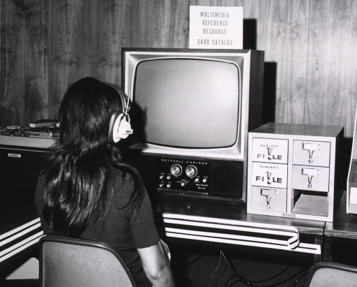 <p>Interior view: a woman with a headset on is sitting in front of the Setchell-Carlson monitor.  On one side of the monitor is a video tape player and on the other side is a subject file catalog.</p>